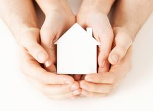 Man and woman hands with white paper house. Real estate and family home concept - closeup picture of male and female hands holding white blank paper house Stock Photos