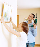 Man and woman  hanging  art picture in frame Stock Photos