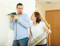 Man and woman  hanging  art picture on wall Royalty Free Stock Photography