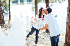 Man and woman hanging clothes baby  on the rope outdoors Royalty Free Stock Photos