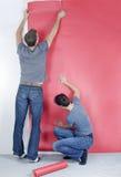 Man and woman hanging wallpaper stock photo