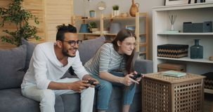 Man and woman happy couple enjoying video game in apartment having fun. Man and woman happy couple are enjoying video game in apartment having fun together stock footage
