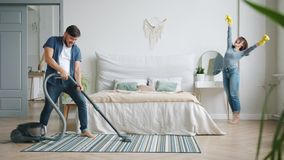 Man and woman having fun during clean-up at home vacuuming and dusting dancing