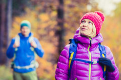 Man and woman happy couple hikers walking in autumn woods Royalty Free Stock Photo