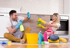 Man and woman happy about finishing chores. Young couple having fun on kitchen floor after finishing chores royalty free stock image