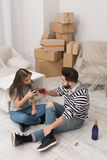 Man and woman are happy to celebrate relocation to newly rented apartment. Royalty Free Stock Photography