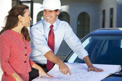 Man & Woman In Hard Hats on Construction Site Stock Images