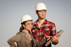 Man and woman in hardhats Stock Images