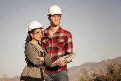 Man and woman in hardhats Royalty Free Stock Photos