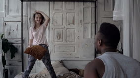 Man and woman have fun in the morning. Multiracial couple in pajamas have fight by pillows. Carefree time. Slow motion. stock video footage