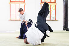 Man and woman having Aikido stick fight. Man and women fighting with wooden stick at Aikido training in martial arts school stock images