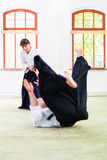 Man and woman having Aikido stick fight Royalty Free Stock Images