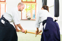Man and woman having Aikido sword fight Stock Image