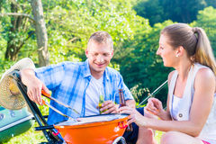 Man and woman having barbeque grilling fish Stock Image