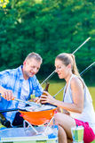 Man and woman having barbeque grilling fish Royalty Free Stock Photo