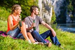 Man and woman having break hiking at river Stock Image