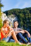 Man and woman having break hiking at river Stock Photo