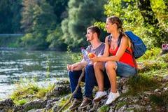 Man and woman having break hiking at river Stock Images