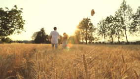 Man and woman having fun across a wheat field with hat. A young couple in love running across a wheat field in the middle of nature in sunset light hand to hand stock video footage