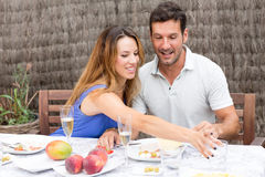 Man and woman having fun during breakfest. Happy couple having food in garden Stock Images