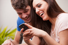 Man and woman having fun with their mobile phones Stock Images