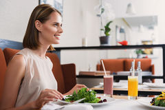 Man and woman having lunch at cafe. How was your day. Young woman eating salad at restaurant and looking at her interlocutor, smiling Royalty Free Stock Images