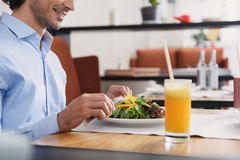 Man and woman having lunch at cafe. Taking break in cafe. Cropped shot of businessman having lunch in cafe, sitting at table and eating salad, holding cutlery in stock photography