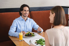 Man and woman having lunch at cafe. What do you think of this salad. Cute couple spending time in cafe on date and having lunch while eating healthy foods stock images
