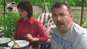 Man and woman having lunch in the garden stock footage