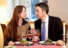 Man and Woman Having a Meal Together. Man and women staring at each other over a meal Stock Photography
