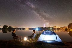 Man and woman having a rest on shore under night sky stock images