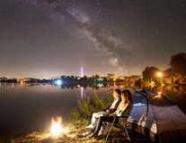 Man and woman having a rest on shore under night sky stock photography