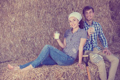 Man and woman in hay with milk Royalty Free Stock Image