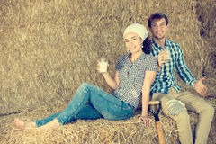 Man and woman in hay with milk Stock Photo