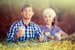 Man and woman in hay with milk Stock Image