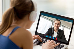 Man and woman in headphones communicating online by video call. Man and women in headphones communicating online by video call, looking at full screen Stock Images