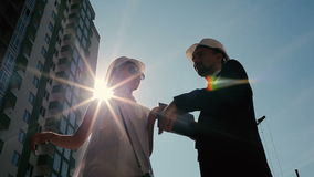 Man and woman in helmet talking near construction stock video