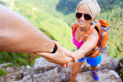Man and woman helping hand in mountains. Helping hand couple, hiking help each other. Man and women teamwork climbing or hiking with motivation and inspiration stock photos