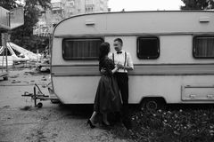 Man and woman is hidden from view behind a trailer Stock Photo