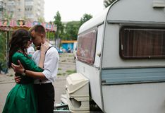 Man and woman is hidden from view behind a trailer Stock Images