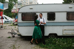 Man and woman is hidden from view behind a trailer Stock Image