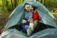 Man and woman hikers sitting within tent in the Royalty Free Stock Images