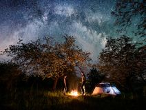 Man and woman hikers standing at a campfire near tent under trees and night sky full of stars and milky way Royalty Free Stock Images