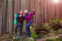 Man and Woman Hikers Staying in Dense Old Forest Smiling and Pointing Stock Photography