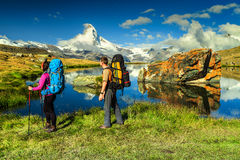 Man and woman hikers trekking in mountains, Valais, Zermatt, Switzerland. Young couple walking with backpack and camping equipment on the mountain trail, near royalty free stock photography
