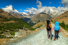 Man and woman hikers trekking in mountains,Valais,Zermatt,Switzerland. Young couple walking with backpacks on the mountain trail,Valais region,Zermatt Royalty Free Stock Photo