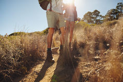 Man and woman hikers walking on dirt trail Stock Image