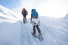 Man and woman hiking with snow shoes through the mountains stock photo