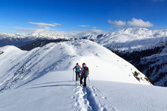 Man and woman hiking on snowshoes and mountain snow panorama with blue sky in Stubai Alps Royalty Free Stock Images