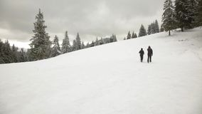 Man and Woman hiking in winter mountains stock footage